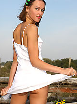 Armour Angels Nippels, Attractive gal plays with her neat white dress while posing outdoors.